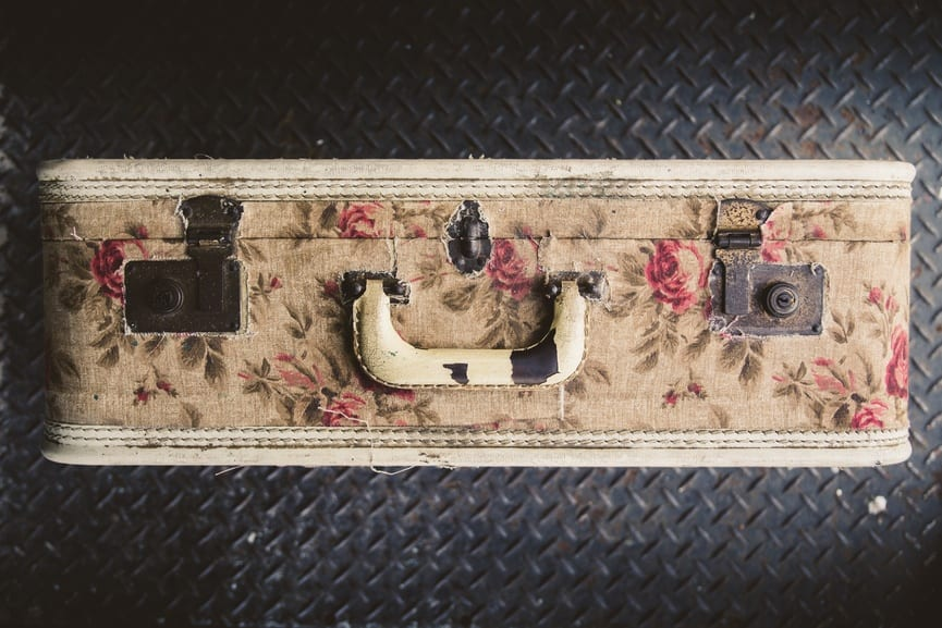 Vintage suitcase with flower pattern on an old train car